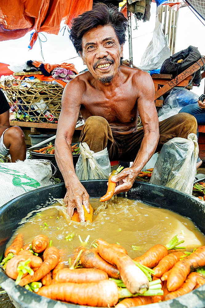 Man washing carrots in a bowl of dirty water, Carbon market, Visayas, Philippines, South East Asia