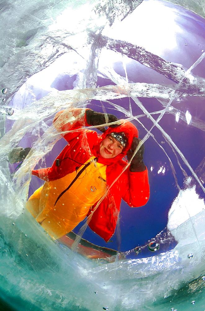 The woman looks through ice lake Baikal, Siberia, Russia, island Olkhon