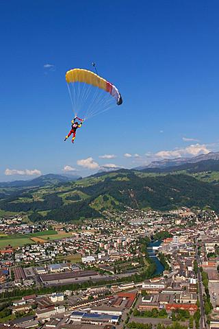 Woman parachuting over rural landscape