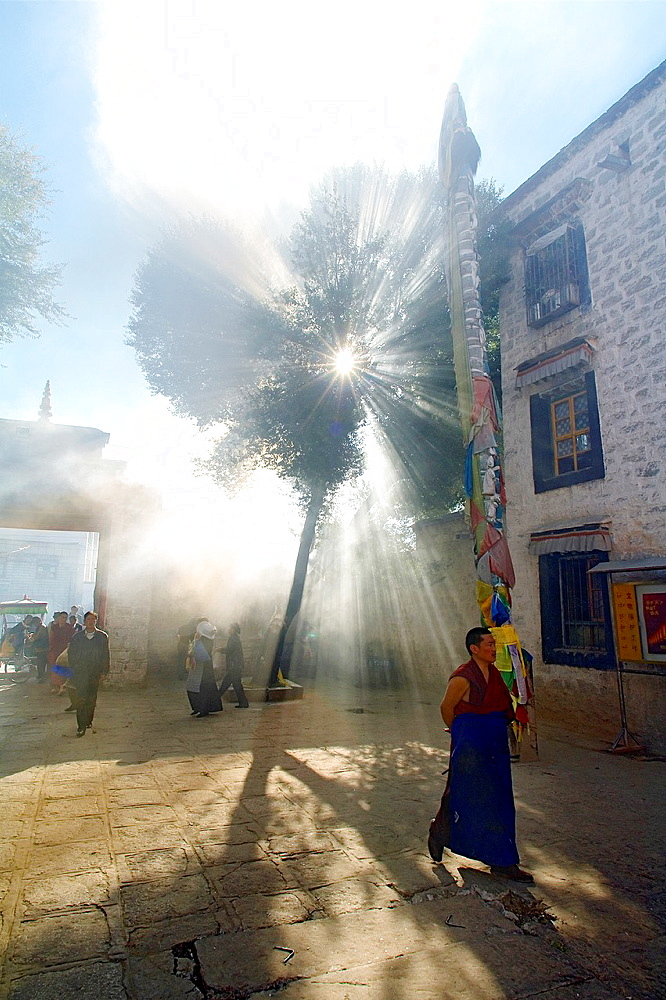 A buddhist monk walk in the smoky courtyard of the Ramoche Monastery lhasa lhasa prefecture tibet china asia