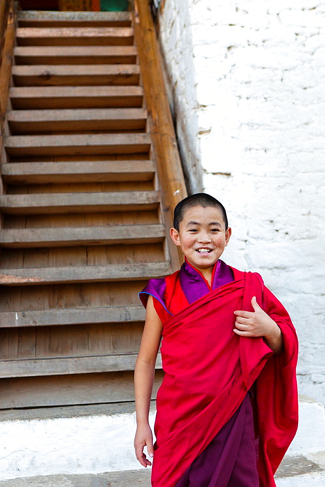 A buddhist novice monk in the stairs of Punakha Dzong, Punakha, Bhutan, Asia.