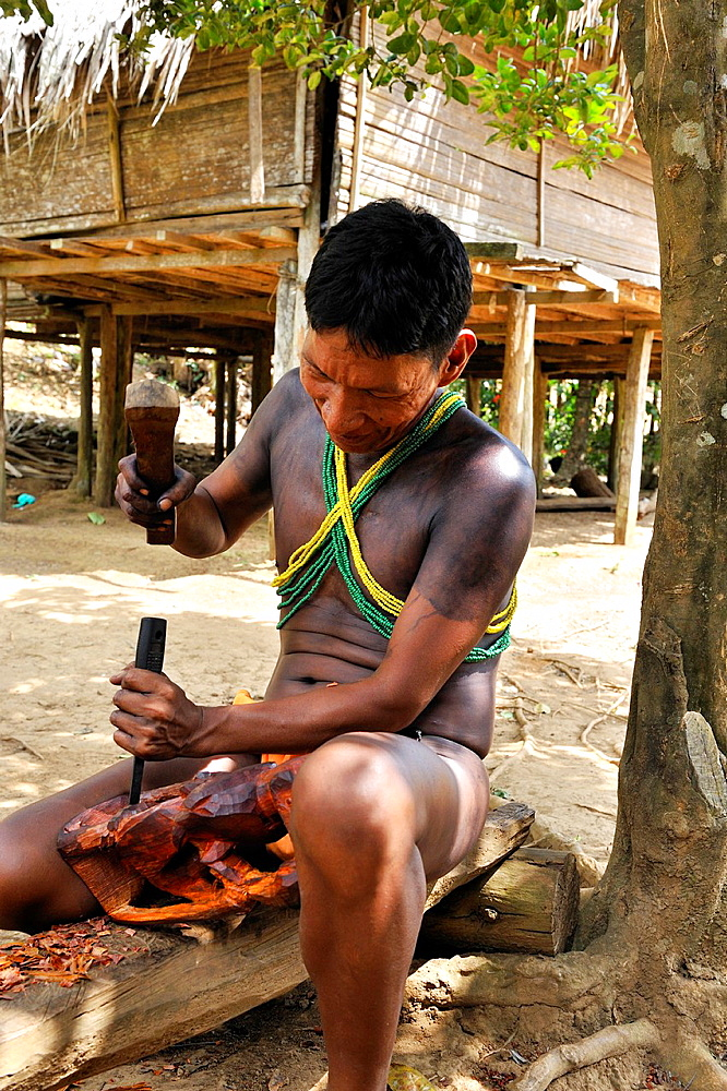 wood carving by a man of Embera native community living by the Chagres River within the Chagres National Park, Republic of Panama, Central America