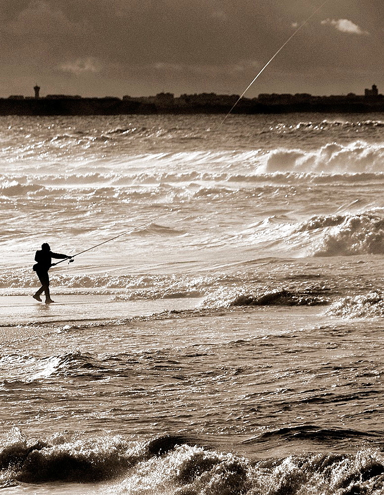 lonely fisherman fishing with a rod directly from Atlantic Ocean, at dusk, Foz do Arelho is a little town on Atlantic Ocean coast and with beautiful Obidos Lagoon, Silver Coast, Portugal