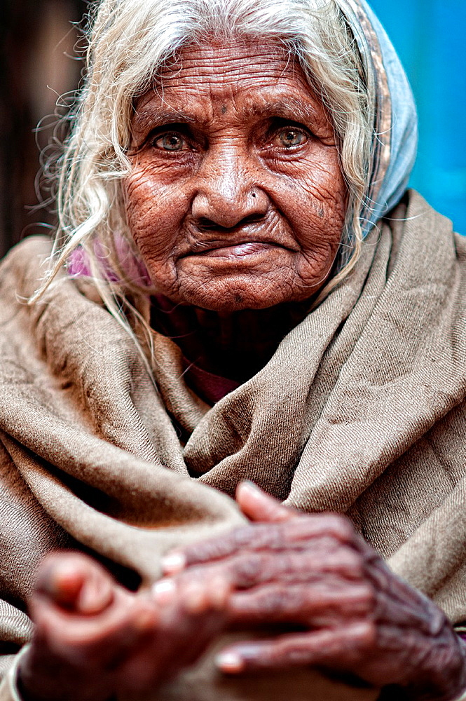 Elder woman begging in the streets of the old town Varanasi, benares, Uttar Pradesh, India