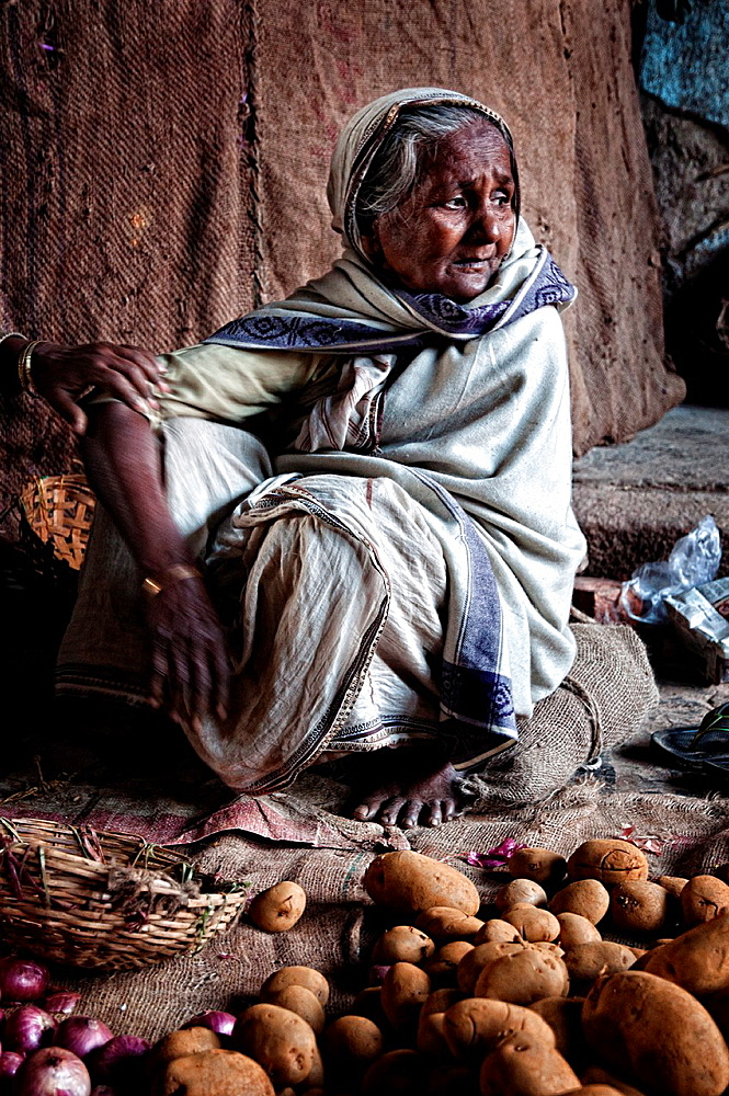 Elder woman selling potatoes in Mullik ghat flower market, Calcutta, West Bengal, India