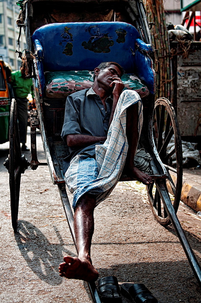 Rickshaw wallah sleeping in the streets of Calcutta, Kolkata, West Bengal, India