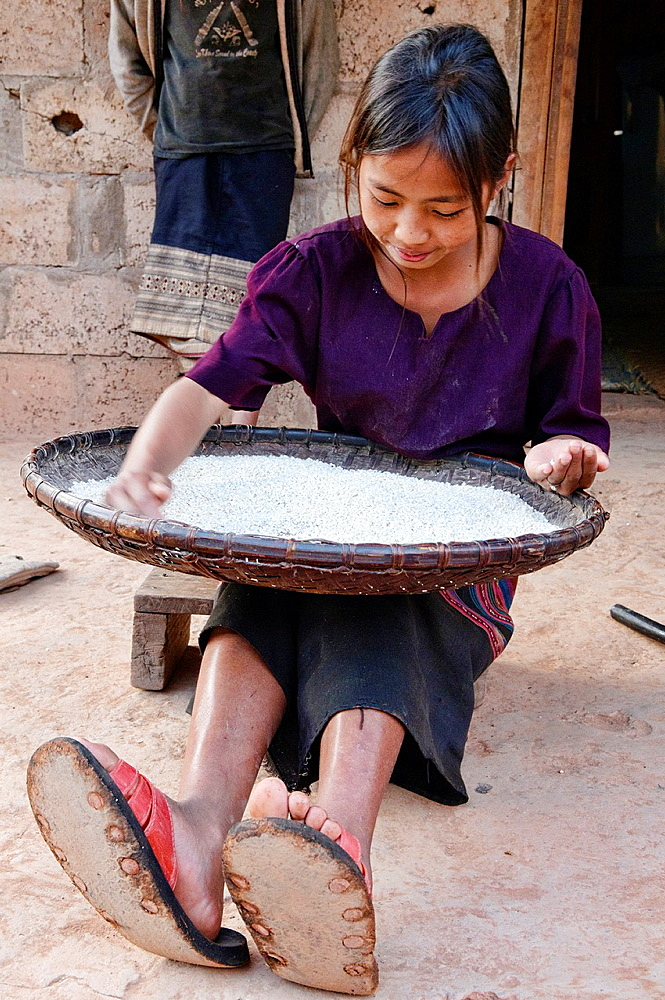 ethnic Khmu girl sifting rice, Luang Nam Tha, Laos