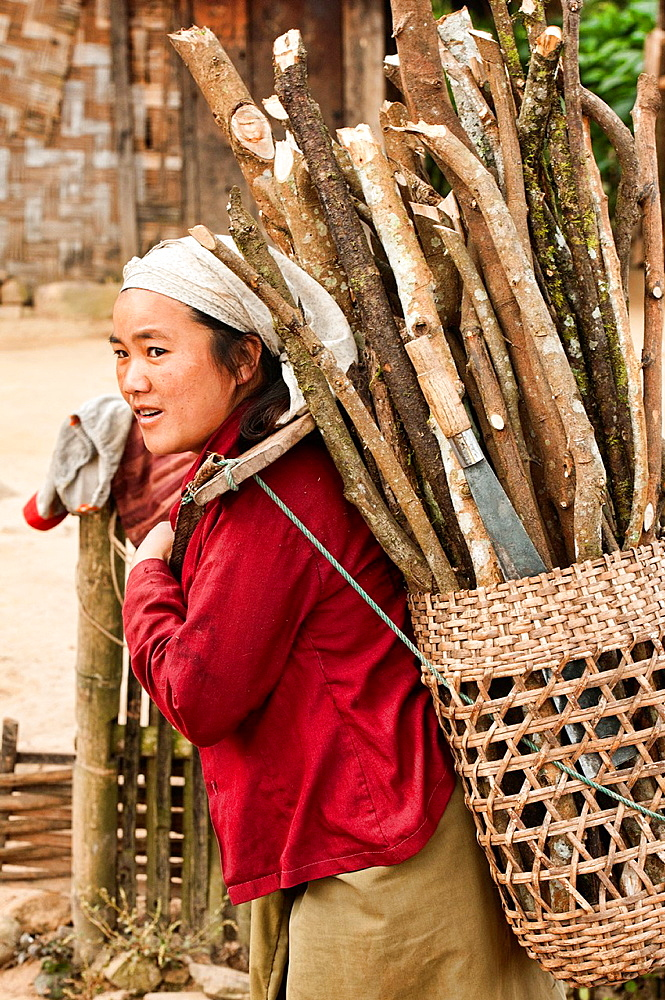 portrait of an ethnic Akha woman and her wood basket, Phongsaly, Laos