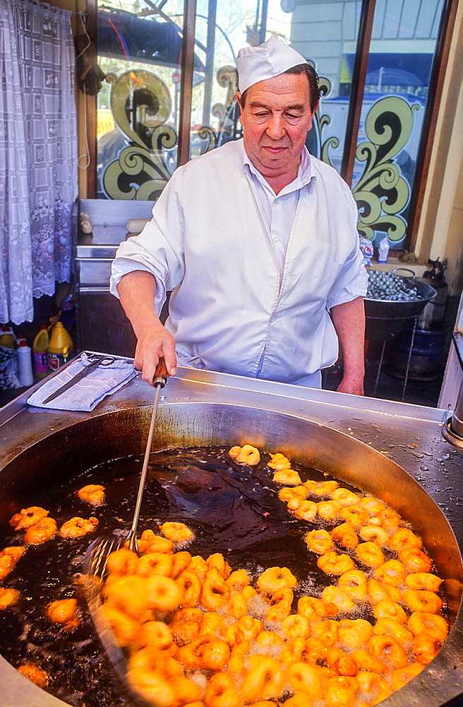 Man cooking bunuelos,a typical Spanish Fritters,Ribera street,Fallas festival,Valencia,Spain