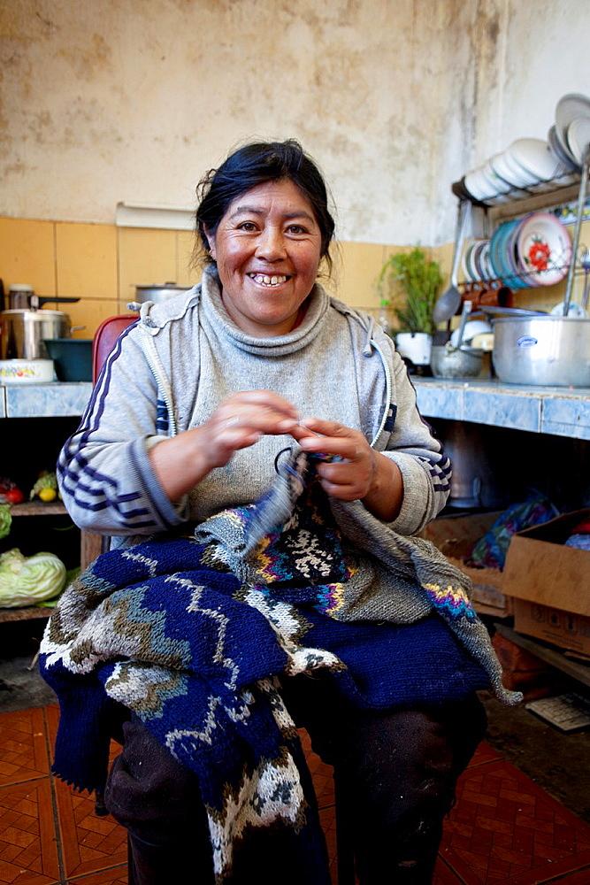 Ecuador, Salinas, Carmen Guaman wknitting for making sweaters.