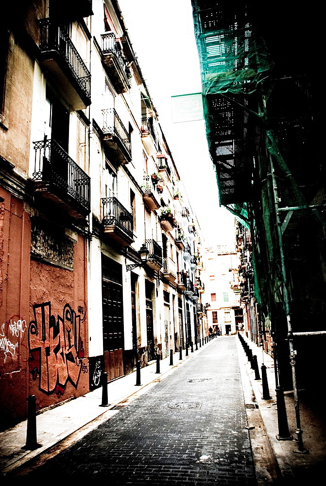 Street in the old area with scaffolding and graffiti. Valencia