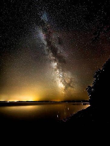 Illuminated night sky over rural landscape