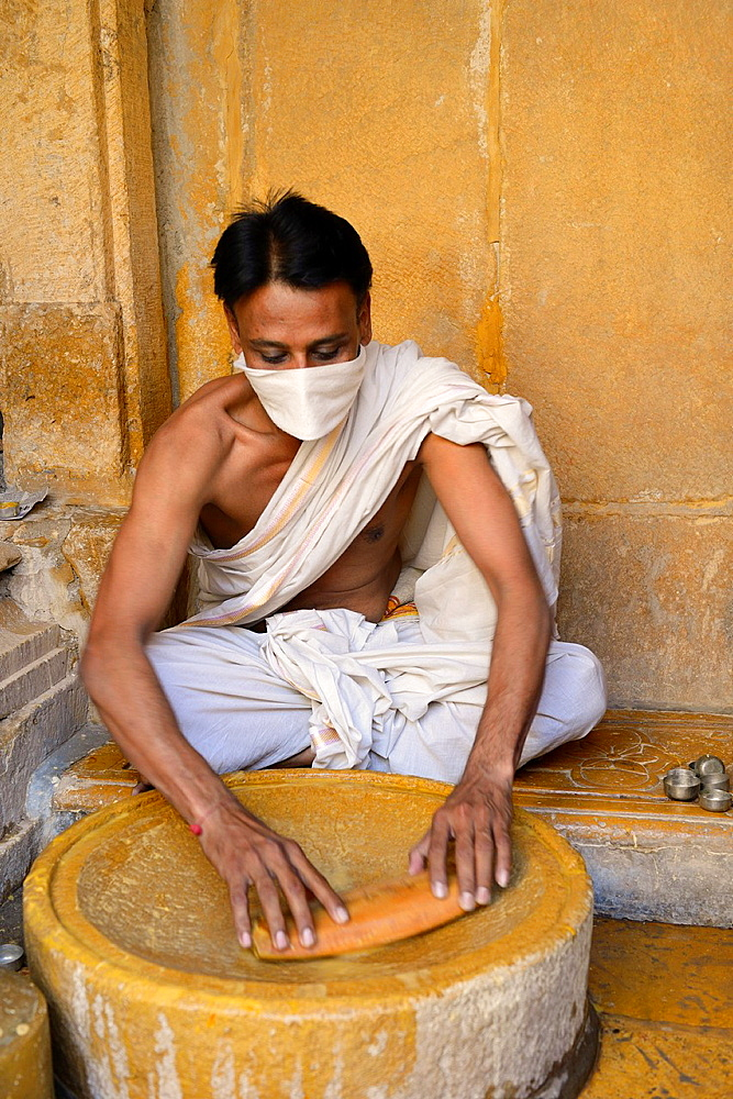 India, Rajasthan, Jaisalmer, Parshvanath temple, Jain devotee preparing sandalwood paste for the worship of the Tirthankaras or ford makers.