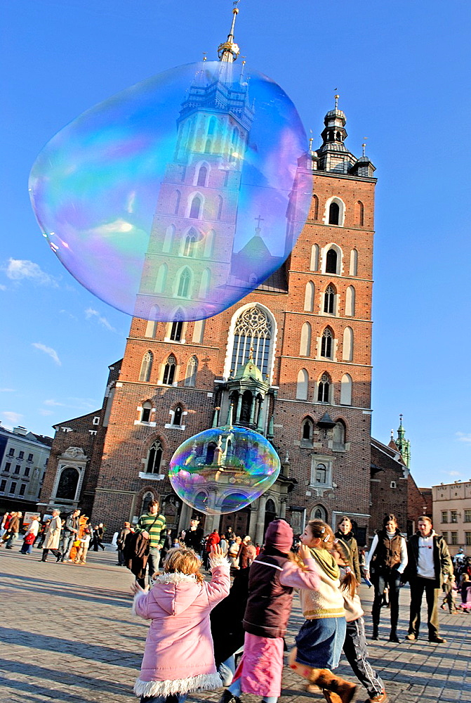 children playing with huge soap bubbles in front of St. Mary's Basilica, Krakow, Poland, Central Europe
