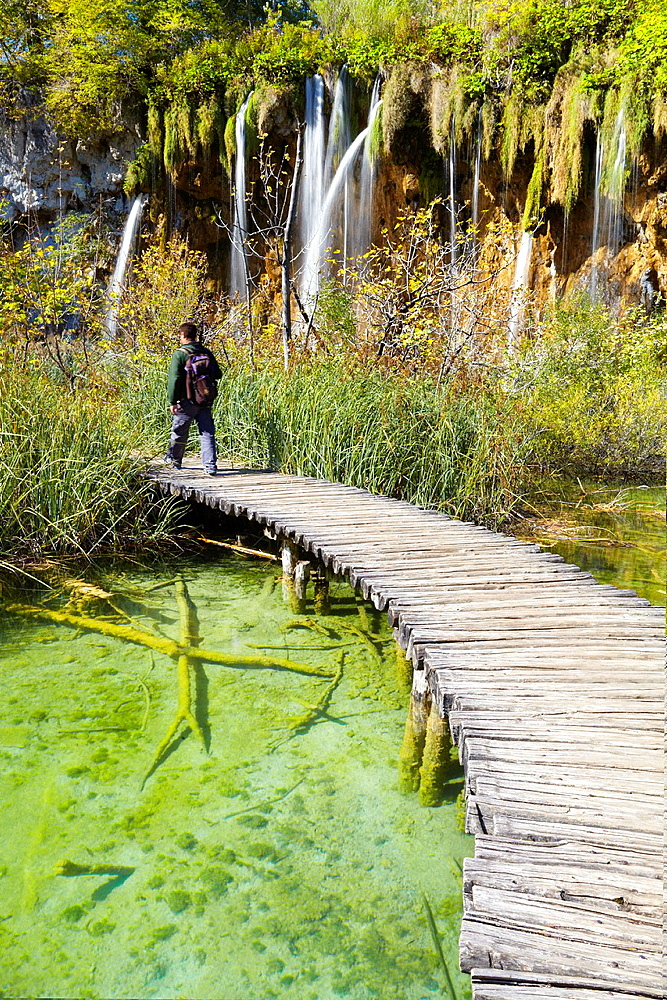Croatia, Plitvice Lakes National Park, water cascade between lakes and wooden footbridge for tourists, central Croatia.