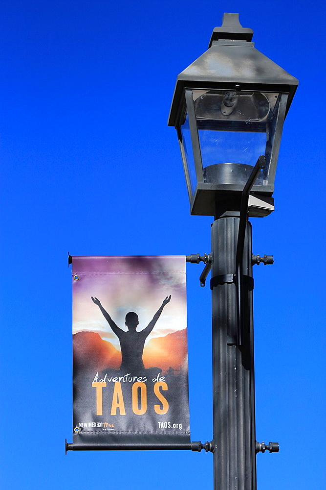 The banner of Taos on a lamp post in Taos Plaza. Taos. New Mexico. USA.