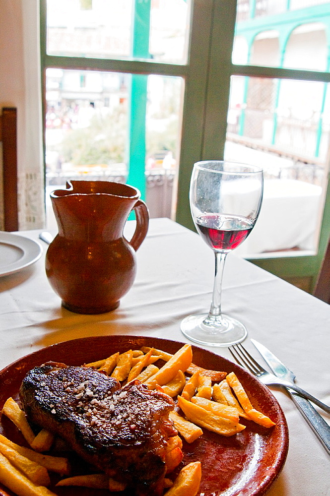 Grilled steak with chips in a typical restaurant. Chinchon, Madrid province, Spain.