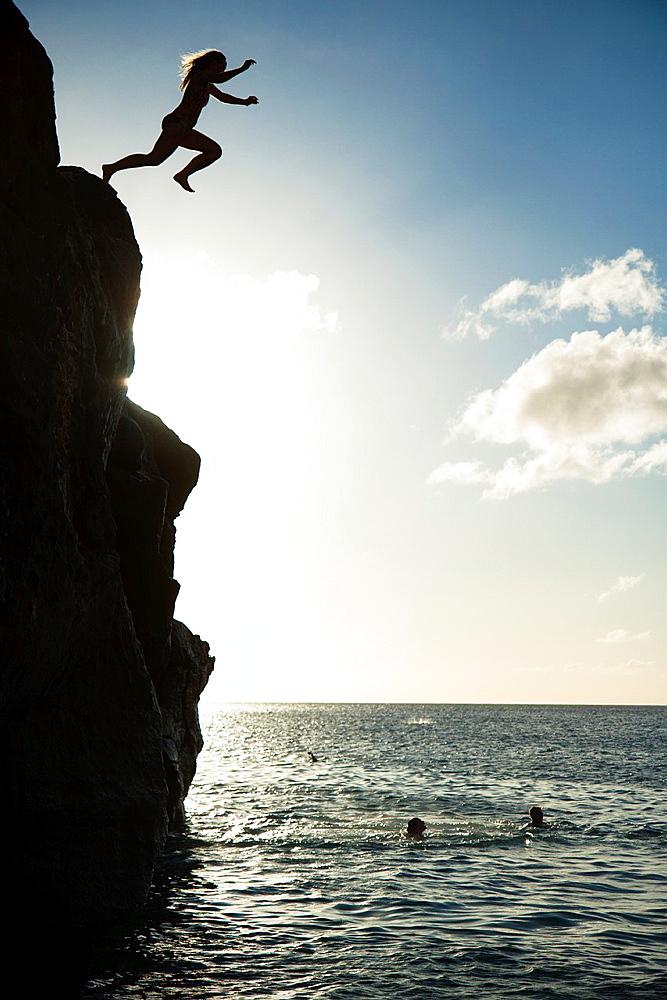 Girl jumping into water, Waimea Bay, Oahu, Hawaii.