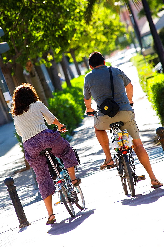 Couple of european people on bycicle. Valencia City, Spain.