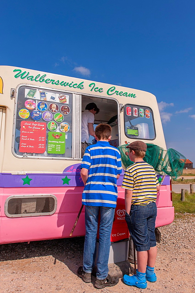 Walberswick, Suffolk, UK. 6th May 2013. Two boys enjoy the sunny weather on Bank Holiday Monday 6th of May 2013 as they buy ice creams at Walberswick, Suffolk, England, Britain, Uk.