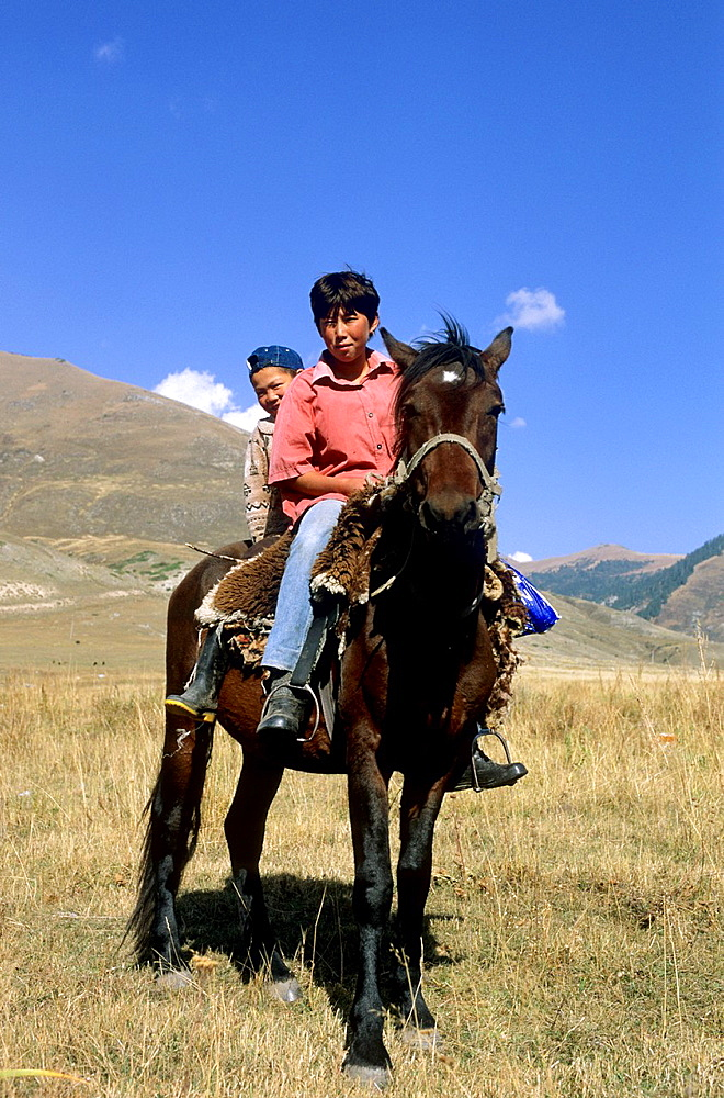 Kyrgyz Rider, Mountains, Local People, guarded the Horses, small and big Boy on here own hors, Kyrgyzstan.