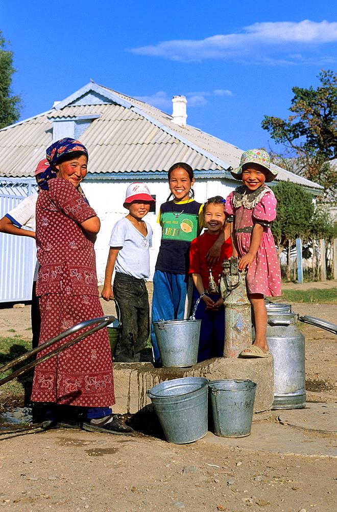Local People and Kids, Issyk Kul Lake, Kyrgyzstan, water jug, poor people.