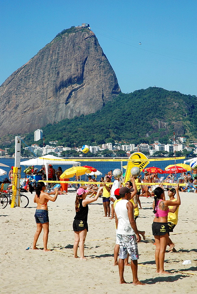 Rio de Janeiro, Brazil, people playing beach-volley at Praia do Flamengo, the Pao de Acucar on the background