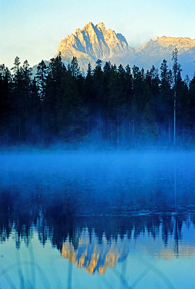 Sawtooth Mountains, Mount Heyburn reflected in Little Redfish Lake during a misty sunrise in the Sawtooth Mountains of central Idaho.