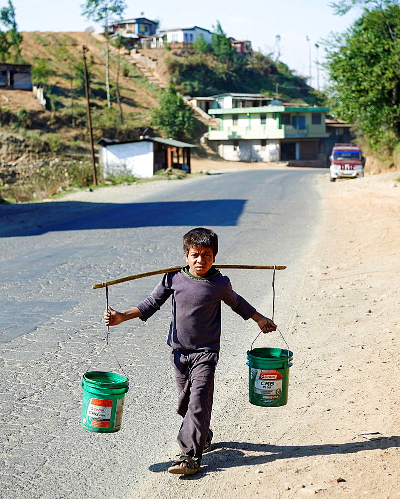 A young boy balances two green buckets while walking on the side of a road to a house.