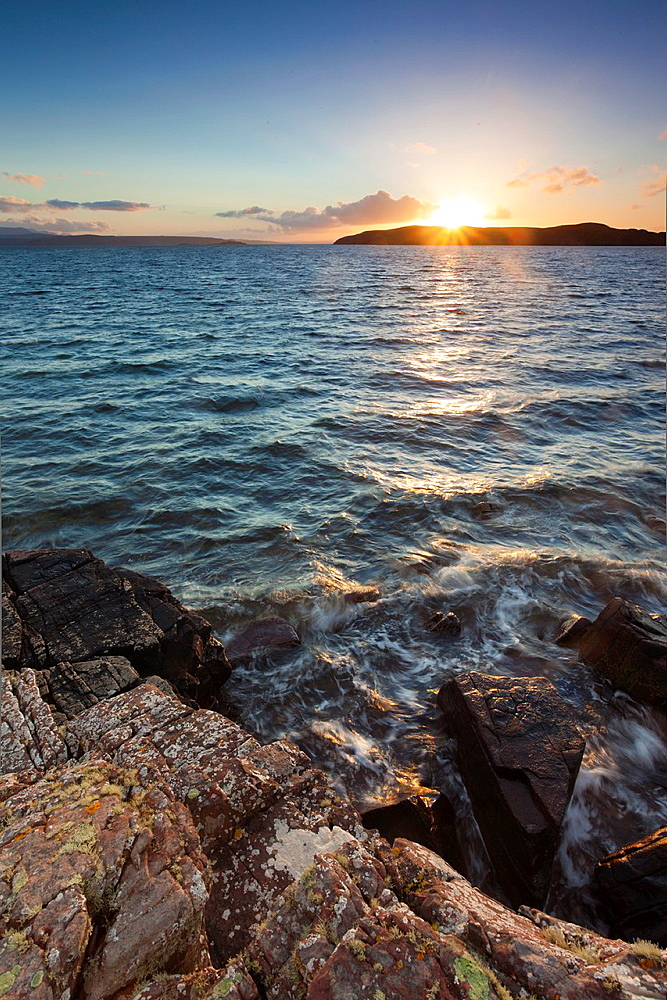 Sun setting behind Horse Island near the Summer Isles in the Highlands of Scotland.