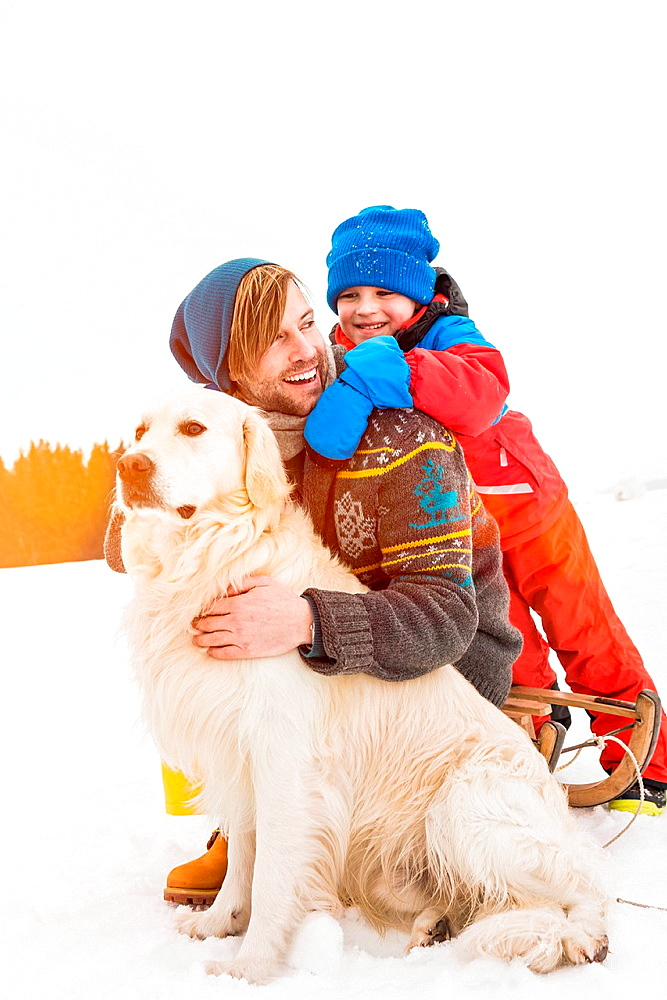 Father and son with dog in snow