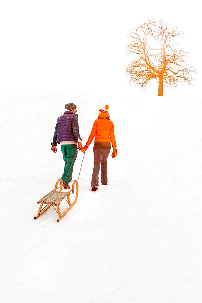 Couple pulling toboggan in snow