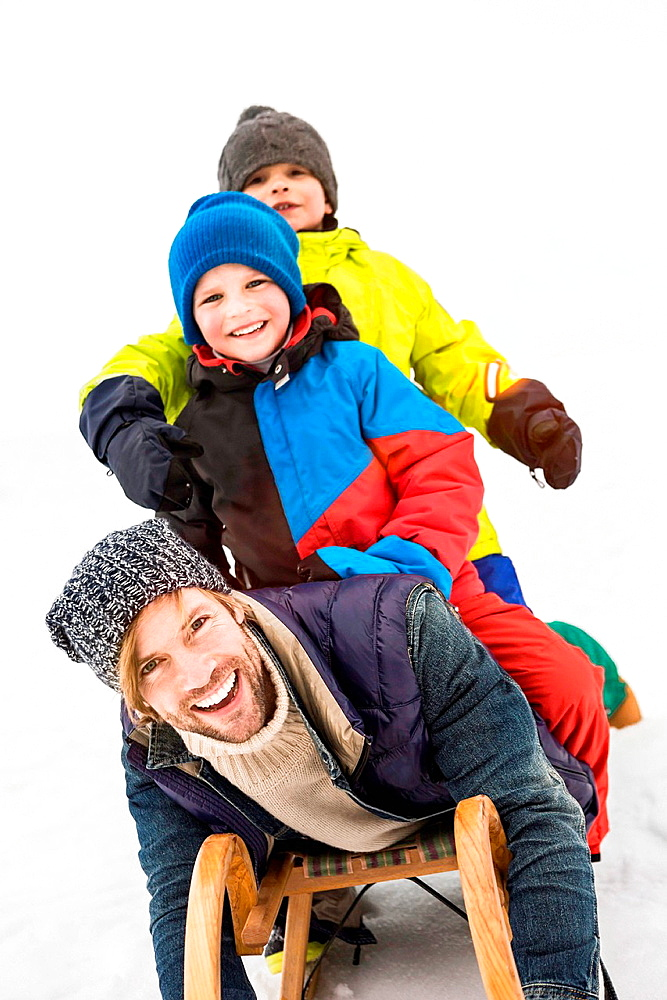 Father with two boys on toboggan in snow
