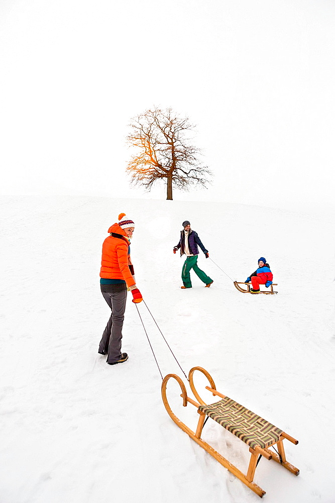 Woman pulling toboggan in snow