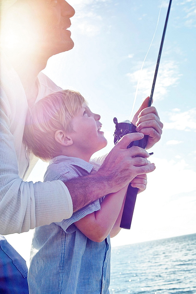 Grandfather and grandson holding fishing rod, Utvalnas, Sweden