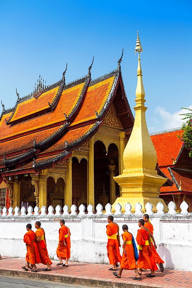 Young novice monks walk past Wat Sop in Luang Prabang, Laos.