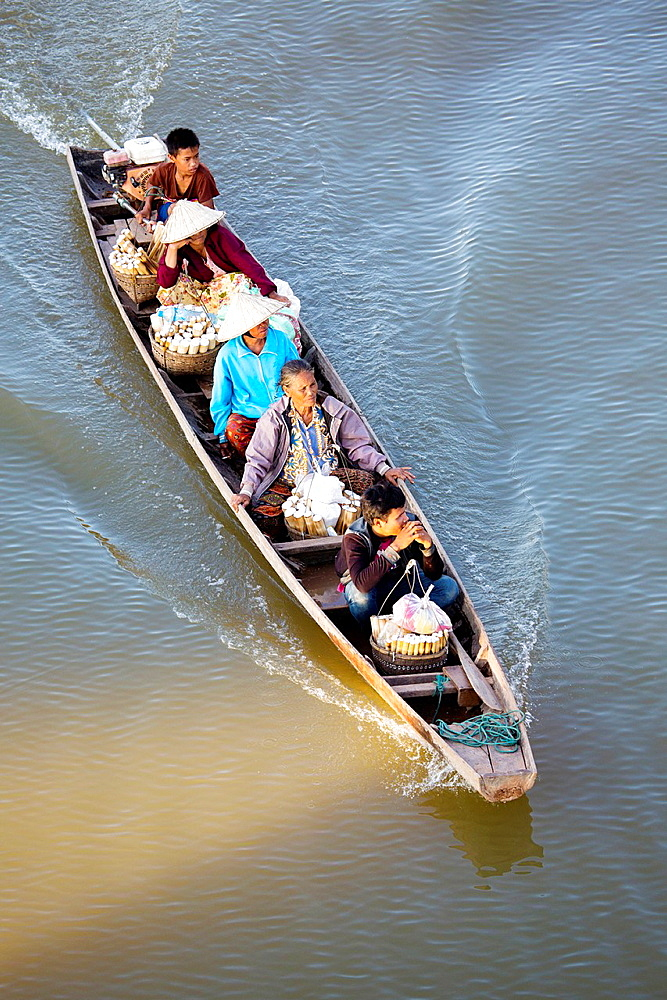 Lao people taking rice to market on the river in Paske, Laos.