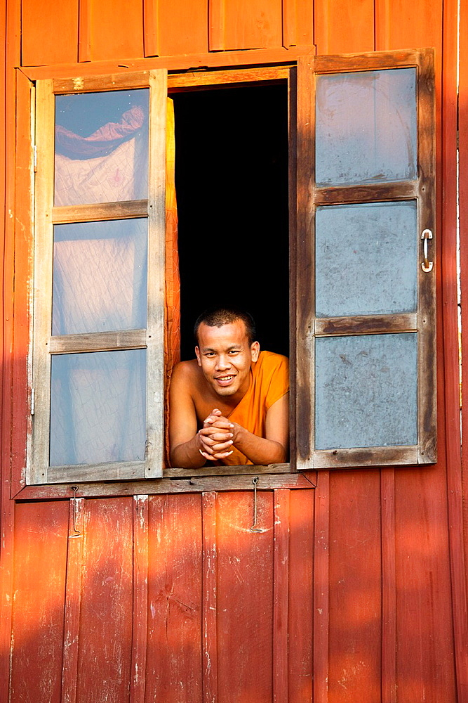 Buddhist monk in the window of his house in Paske, Laos.