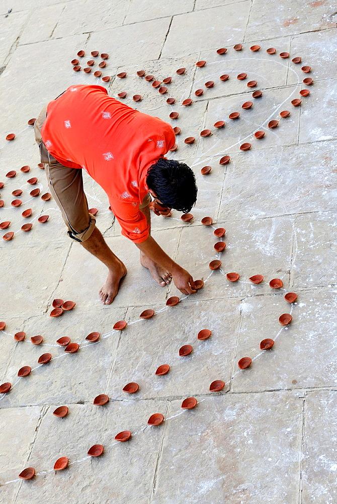 India, Uttar Pradesh, Varanasi, Dev Deepawali festival, Hindu devotee setting earthen lamps.