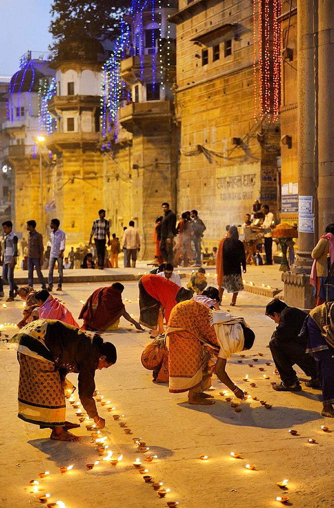 India, Uttar Pradesh, Varanasi, Dev Deepawali festival, Hindu devotees lighting oil lamps.