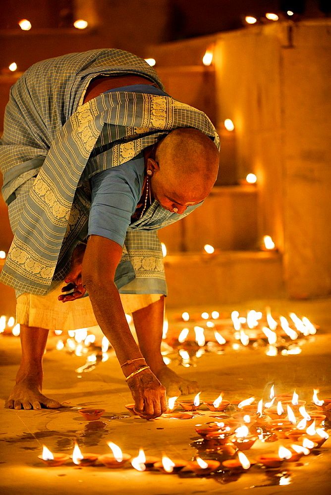 India, Uttar Pradesh, Varanasi, Dev Deepawali festival, Hindu devotee lighting oil lamps.