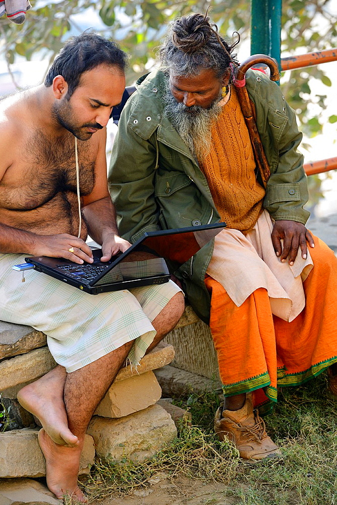 India, Uttar Pradesh, Varanasi, Hindu devotee and sadhu (ascetic) surfing on Internet.