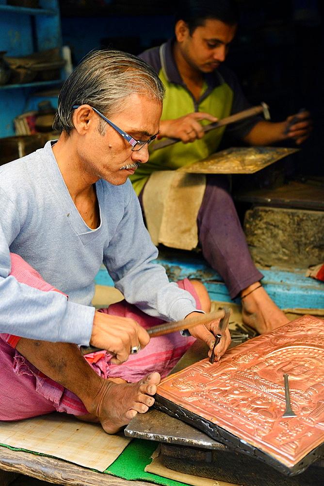 India, Uttar Pradesh, Varanasi, Craftsmen embossing copper plates.