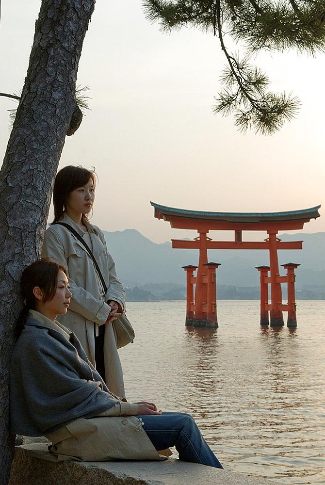 women along the sea near itsukushima shrine torii temple gate, miyajima island, near Hiroshima Japan