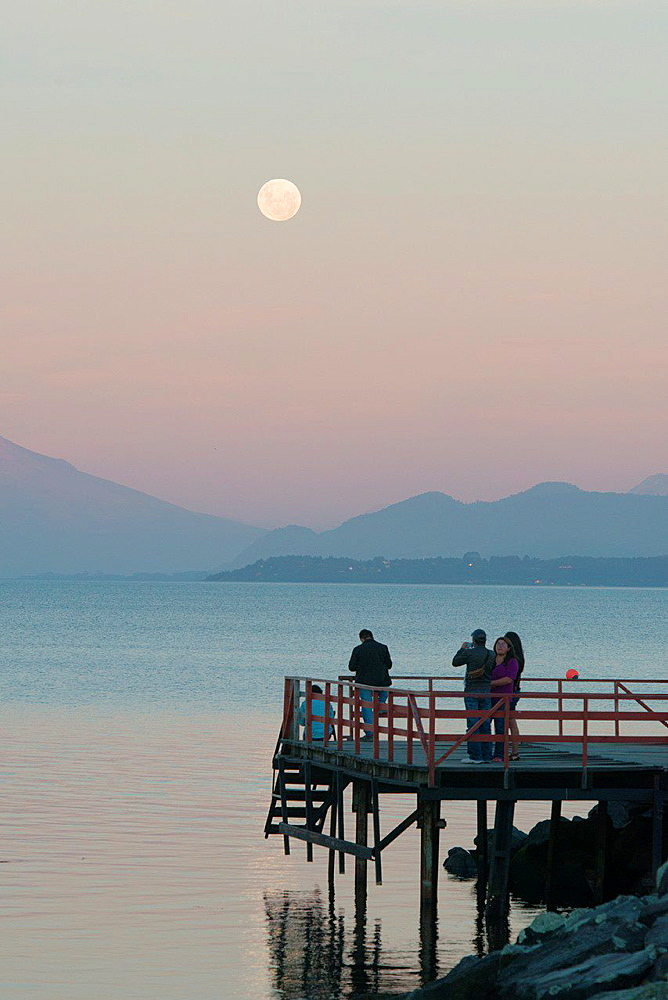 Tourists on Dock watching Moon, Puerto Varas, Chile with Osorno Volcano and Llanquihue Lake.