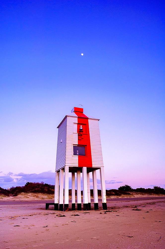 Burnham-on-Sea Lighthouse at dusk with the moon shining overhead. Somerset, England.