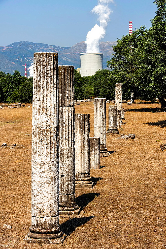 Columns from the ruins of Ancient Megalopolis with the cooling tower and chimney of Mergalopoli's modern power station in the background. Central Peloponnese, Greece.
