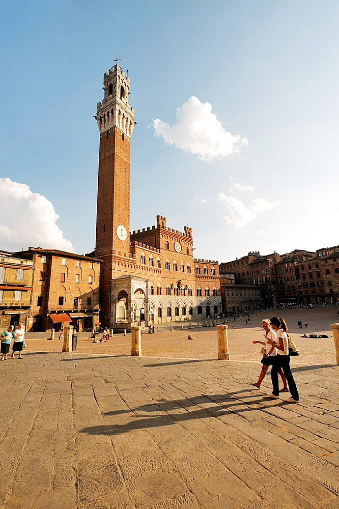 Tourists in the Piazza del Campo, the central square of the city of Sienna, Tuscany, Italy. Torre del Mangia tower rises behind.