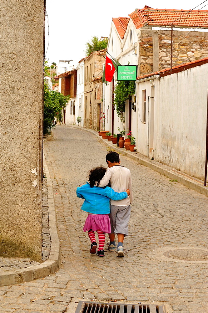 Boy and girl walking in old street with arms around each other, Bozcaada, Turkey
