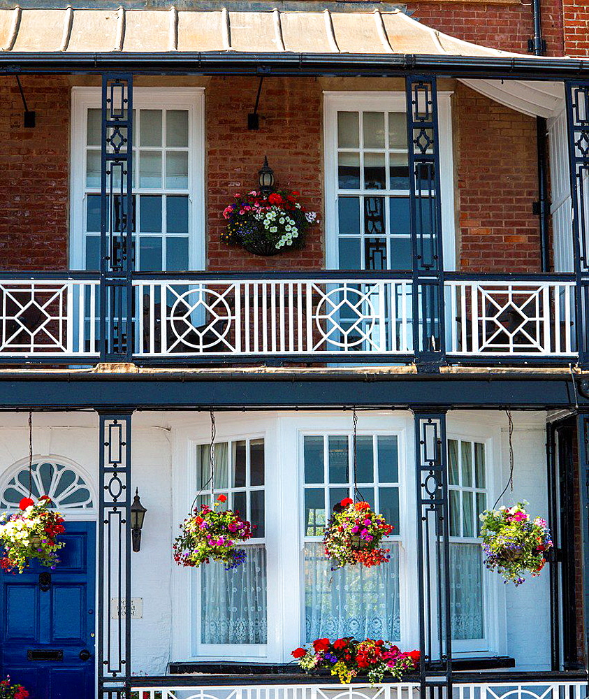 House with flower baskets and balconies on the seafront at Sidmouth, Devon, England.